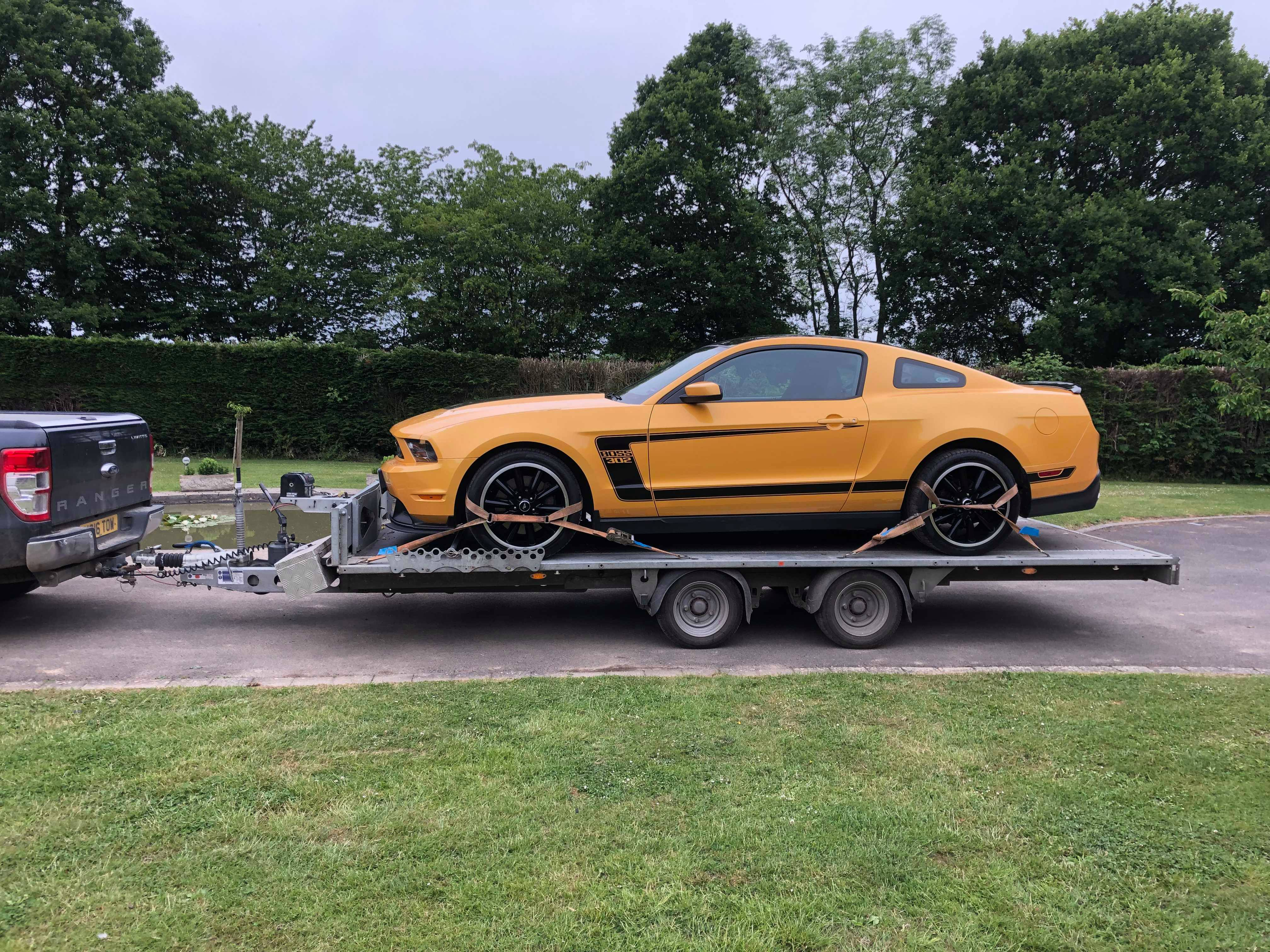 A 16.5 x 6.5 ft Tilt bed trailer holding a Yellow Boss Mustang strapped down securely being towed by a Ford Ranger truck.